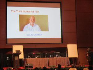 Photo of a large screen at a conference showing the Third Workforce film