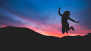 Silhouette of a person jumping with the sun setting behind mountains