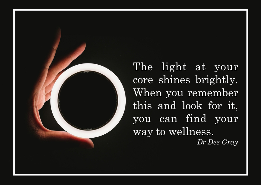 Hand holding an illuminated circle, with the text 'The light at your core shines brightly. When you remember this and look for it, you can find your way to wellness. Dee Gray.'